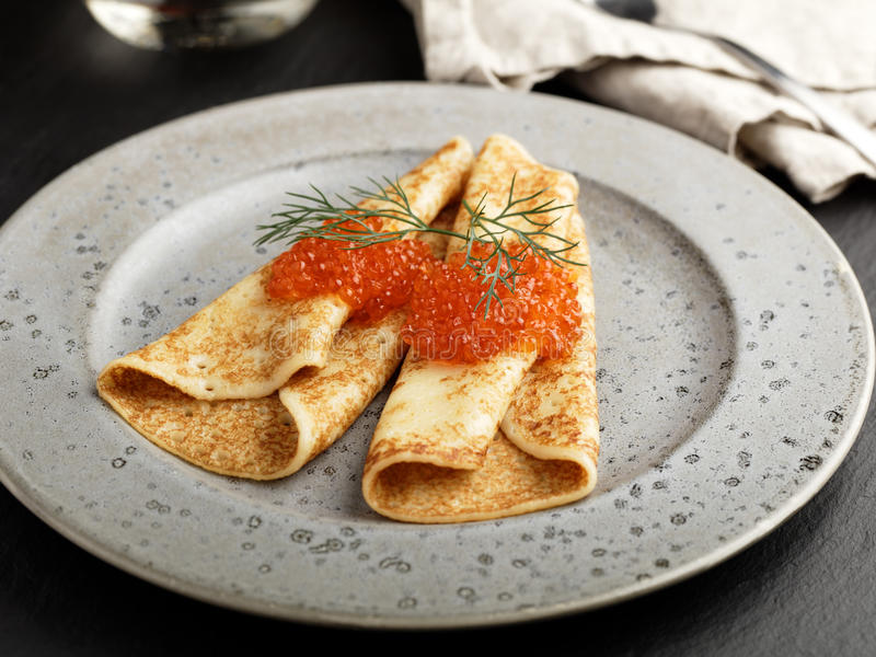 俄国俄式薄煎饼用在一个灰色板材特写镜头的红色鱼子酱 免版税库存照片