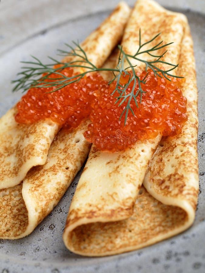 俄国俄式薄煎饼用在一个灰色板材特写镜头的红色鱼子酱 免版税图库摄影