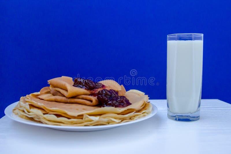 俄国俄式薄煎饼薄煎饼witg杯在蓝色背景的牛奶 Foodphotography 图库摄影