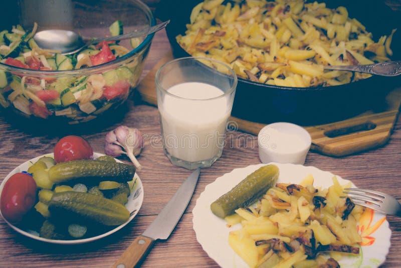 俄国全国烹调:油煎的土豆用酱瓜,牛奶,大蒜 免版税库存图片