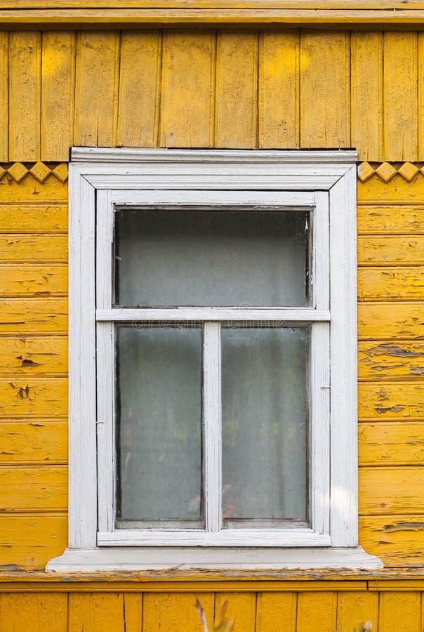 俄国农村房子、黄色墙壁和白色窗口 免版税库存照片