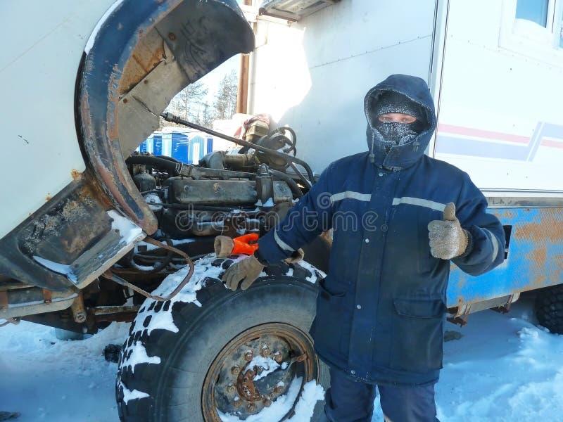 俄国卡车修理在寒冷的 供以人员修理卡车在冬天衣裳和结冰从寒冷 免版税库存照片
