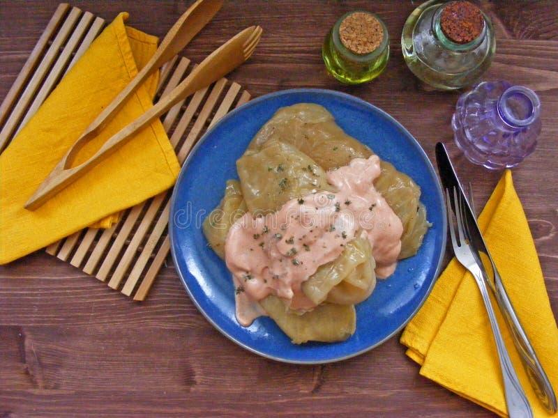 俄国和白俄罗斯语的烹调:白菜卷卷平的看法与膳食和西红柿酱的在木背景 库存图片