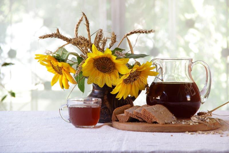 俄国啤酒(kvas)在一个透明水罐、面包和sunflo花束  库存照片