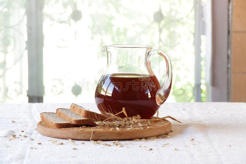 俄国啤酒(kvas)在一个透明水罐和黑麦面包 库存照片