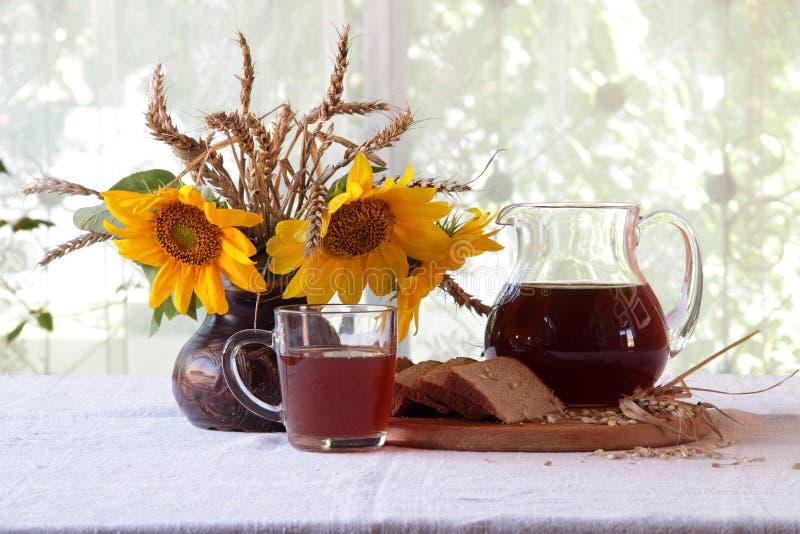 俄国啤酒(kvas)在黑麦发酵、面包和向日葵花束  免版税库存照片