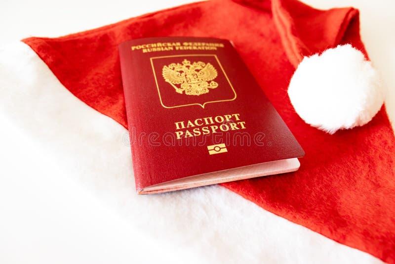 俄国国际护照和圣诞老人帽子在白色背景 库存图片