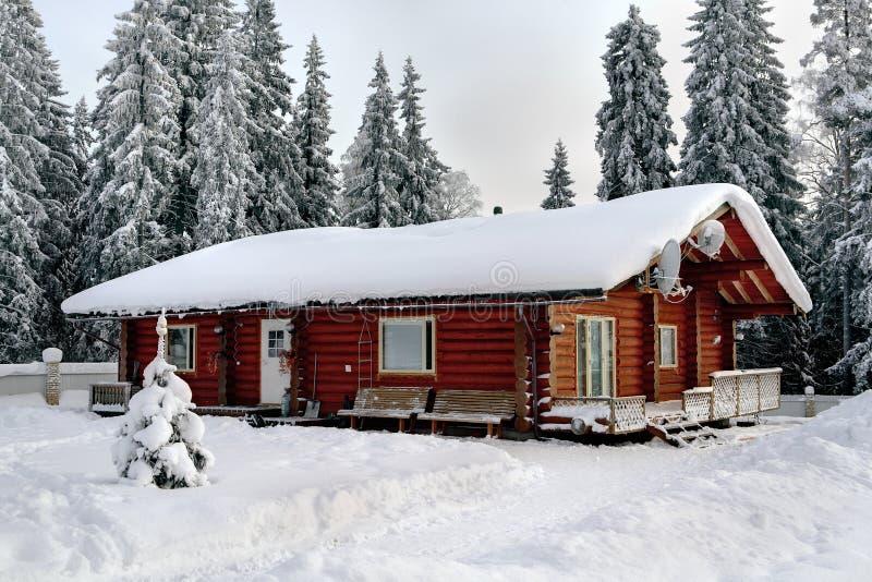 俄国小屋弄脏了日志,在积雪的前面背景  免版税库存图片