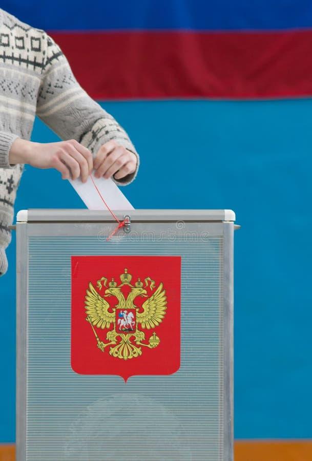 俄国总统选举-一个人投入选票到投票的箱子 免版税库存照片