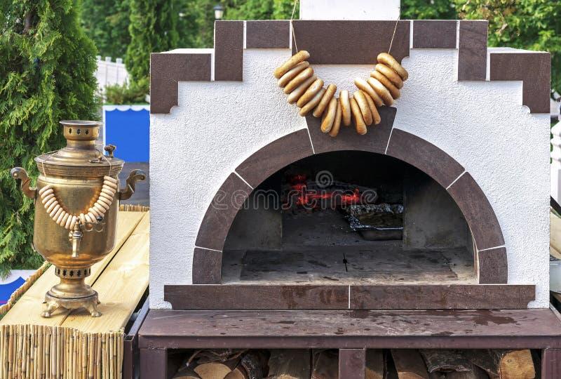 俄国木火炉和古色古香的俄国式茶炊与捆绑百吉卷 免版税库存图片