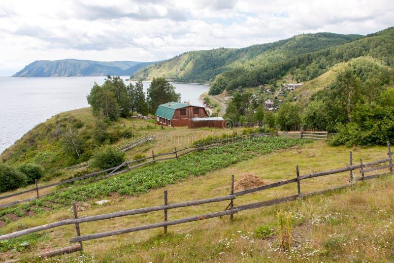 俄国村庄 湖房子的看法倾斜的,在山和森林附近 免版税库存照片