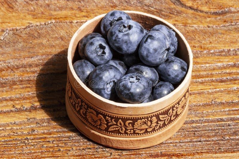 俄国桦树吠声碗在土气木桌上的新鲜的蓝莓 健康有机季节性果子背景 免版税库存照片