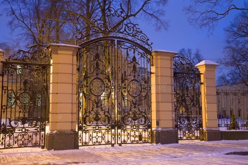 俄国沙皇时代的太子亚历山大米哈伊洛维奇在1月晚上,圣彼得堡宫殿的古老加工铁门  库存照片