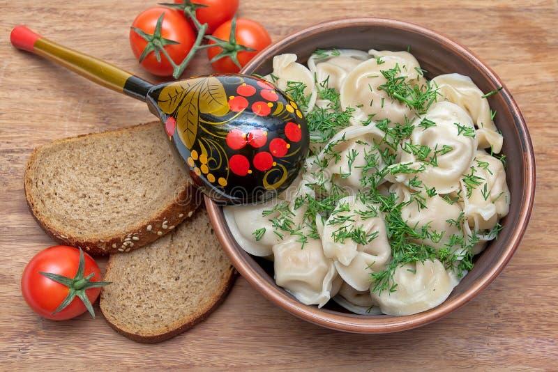 俄国烹调:在板材、西红柿和面包的饺子 免版税库存照片