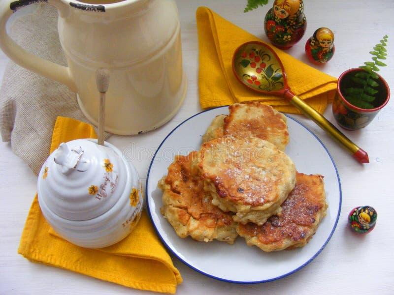 俄国烹调:在板材的绉纱薄煎饼有橡木的在与土气牛奶罐、蜂蜜和嵌套dol的白色木背景剥落 库存图片