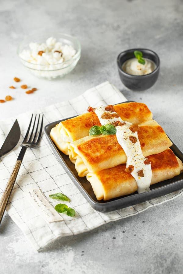 俄国稀薄的薄煎饼用酸奶干酪和葡萄干 健康传统早餐 免版税库存照片