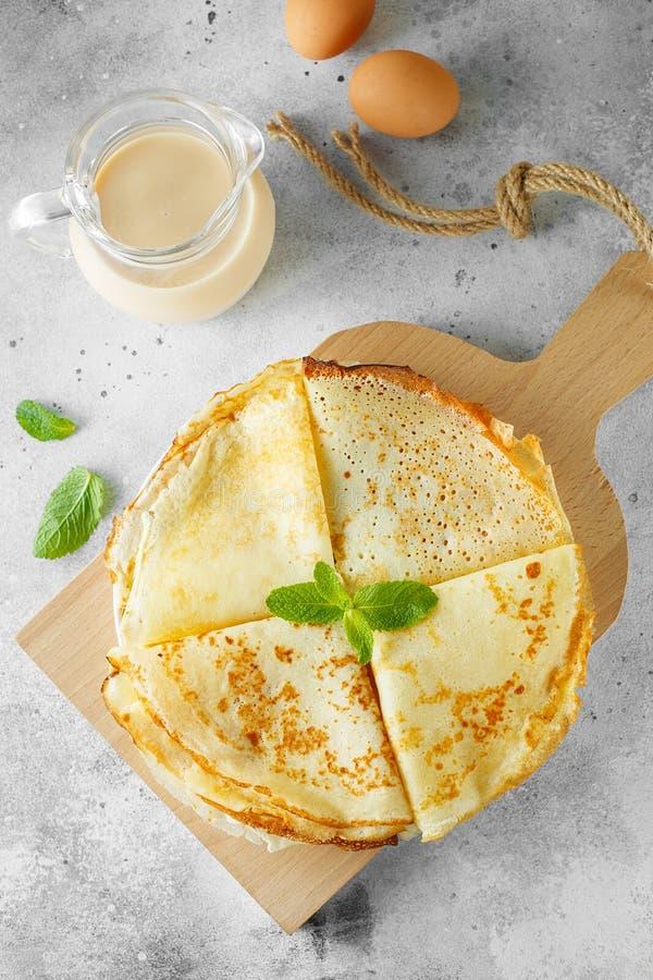 俄国薄煎饼服务与薄荷叶和成份-牛奶和鸡蛋在灰色背景前面 r 免版税库存图片