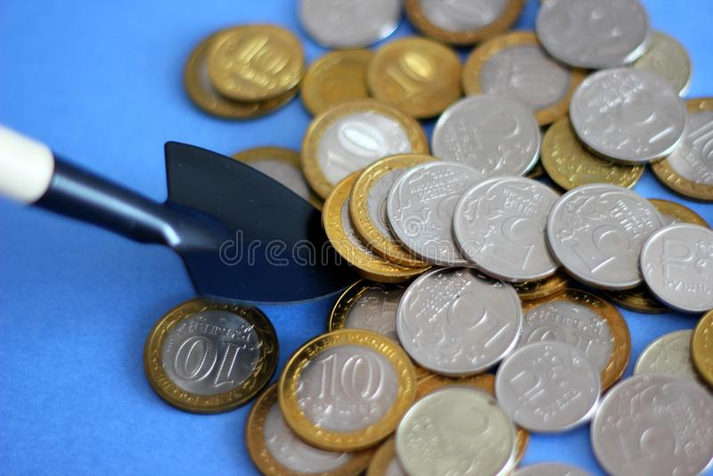 俄国金属货币1,2,5 10卢布在铁锹、储积的在色的背景的概念和财富说谎 免版税库存图片