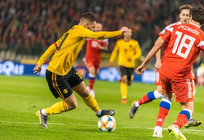 俄罗斯国家队防御者尤里做在比利时全国足球队上尉伊登・夏萨特的日尔科夫一不理智 免版税库存照片