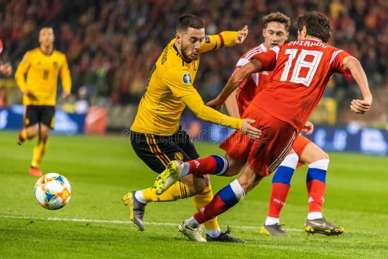 俄罗斯国家队防御者尤里做在比利时全国足球队上尉伊登・夏萨特的日尔科夫一不理智 库存图片