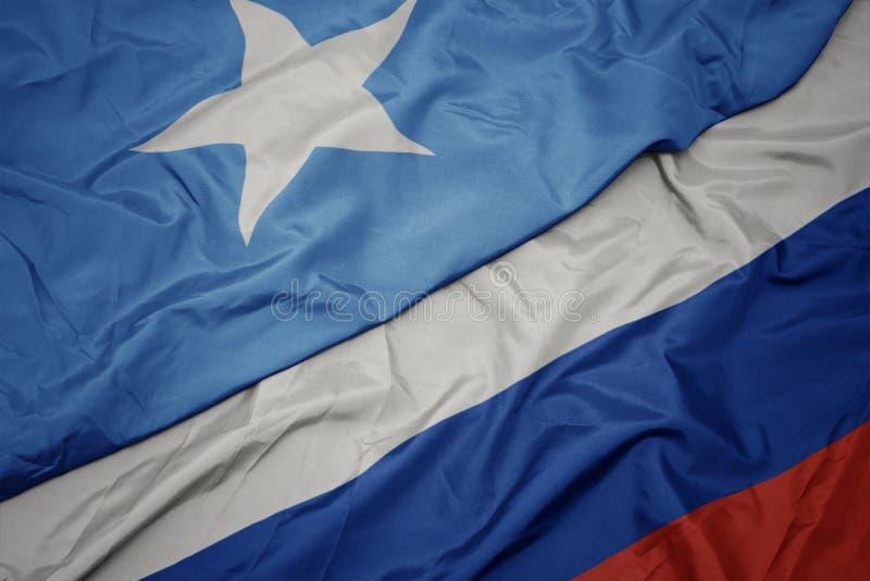 俄罗斯的挥动的五颜六色的旗子和索马里的国旗 免版税库存图片