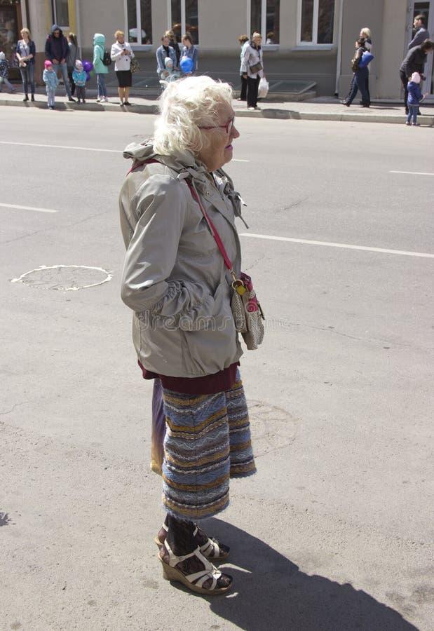 俄罗斯,克拉斯诺亚尔斯克,2019年6月:时兴地打扮了在街道上的老妇人 库存照片
