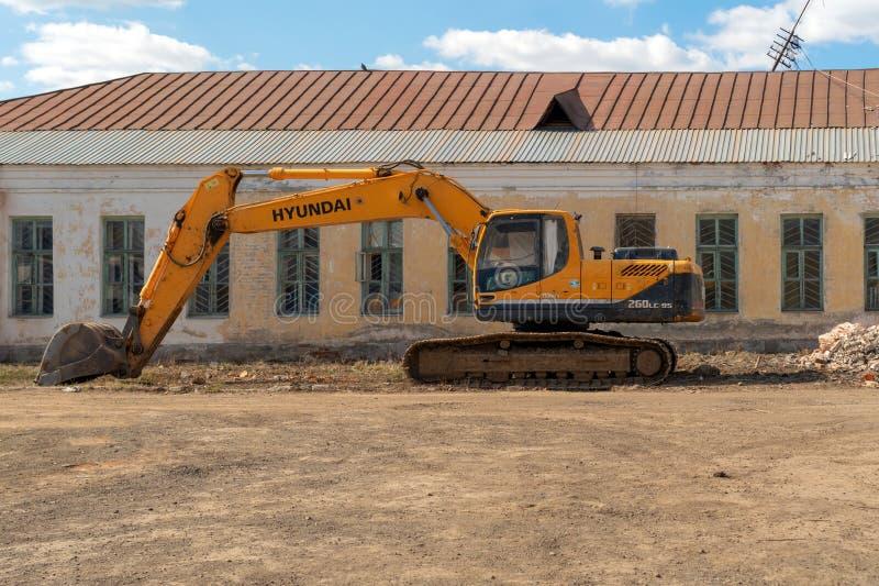 俄罗斯,喀山- 2019年4月20日:在一个被放弃的大厦的背景的黄色挖掘机 免版税库存照片