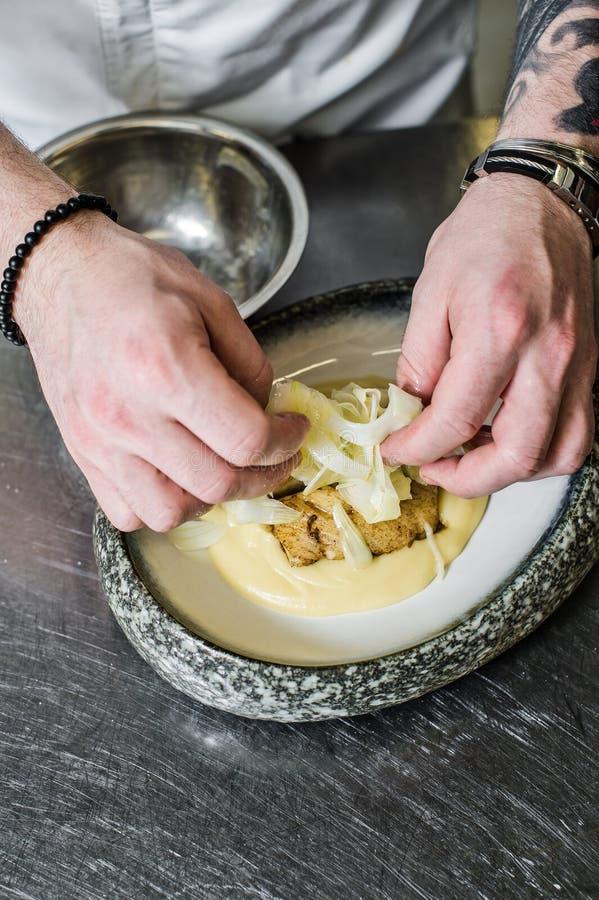 俄罗斯,圣彼德堡,03 17 2019厨师准备大比目鱼在芹菜下在餐馆厨房里 免版税库存图片
