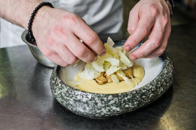 俄罗斯,圣彼德堡,03 17 2019厨师准备大比目鱼在芹菜下在餐馆厨房里 图库摄影