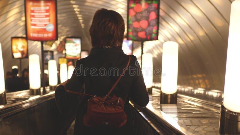 俄罗斯,圣彼德堡, 2017年6月21日 有背包的妇女沿着走地铁自动扶梯 免版税库存图片
