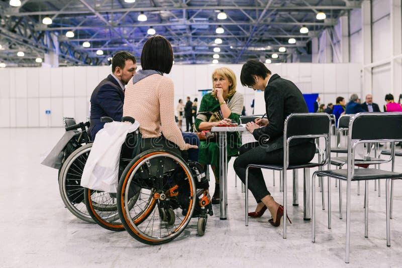 俄罗斯,城市莫斯科- 2017年12月18日:轮椅的年轻女人 一群人谈论项目在a 库存照片