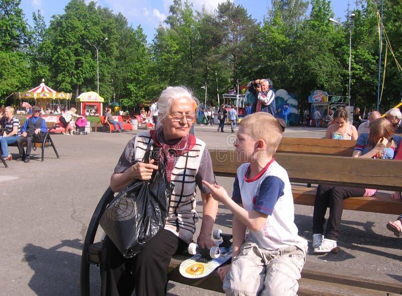 俄罗斯,新西伯利亚,2011年7月21日:老妇人祖母和孙子坐一条长凳在夏天谈的公园 免版税库存照片