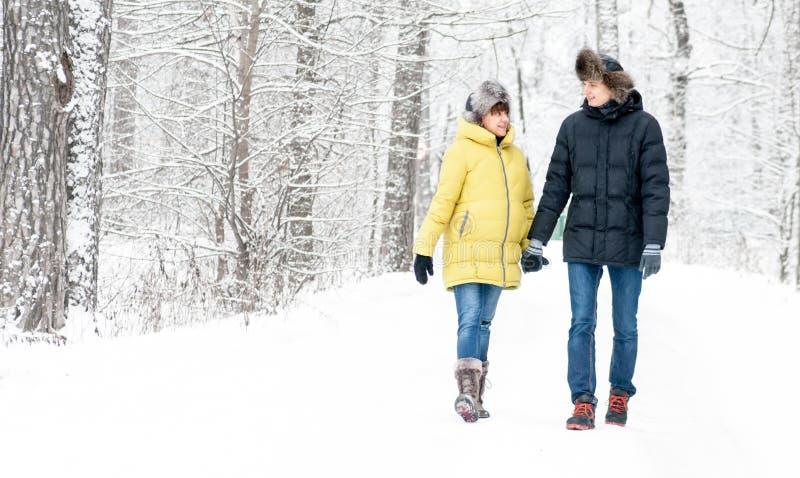 俄罗斯,梁赞2017年1月04日:丈夫拥抱和走与怀孕的妻子在冬天森林里 库存照片