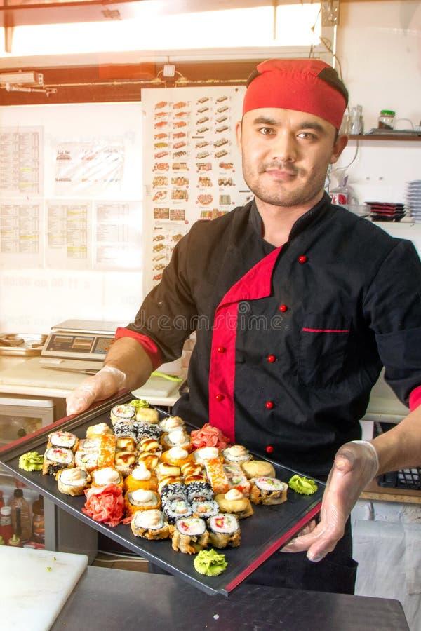俄罗斯,梁赞- 12 11 2018 - 微笑的亚裔厨师用在厨房的寿司 免版税库存图片