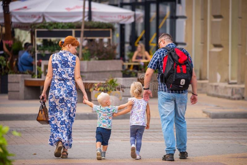 俄罗斯,罗斯托夫On唐,2018年9月09日:与两个逗人喜爱的blondy孩子的幸福家庭步行在城市街道上  图库摄影