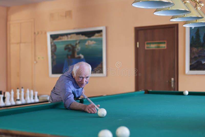 俄罗斯,莫斯科, 2018年4月7日,演奏台球的一个人在老人院,社论 库存照片