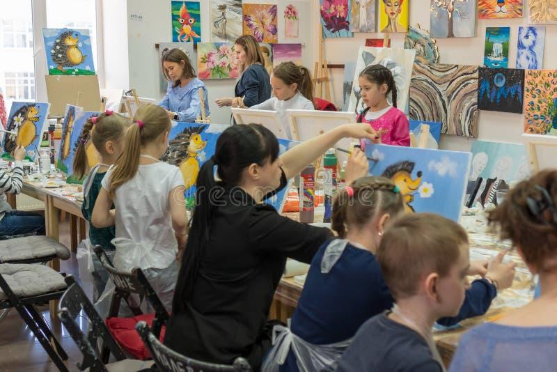 俄罗斯,鞑靼斯坦共和国,2019年4月21日 儿童的图画班 画架,帆布,在桌上的油漆 一个小组儿童凹道 免版税库存图片