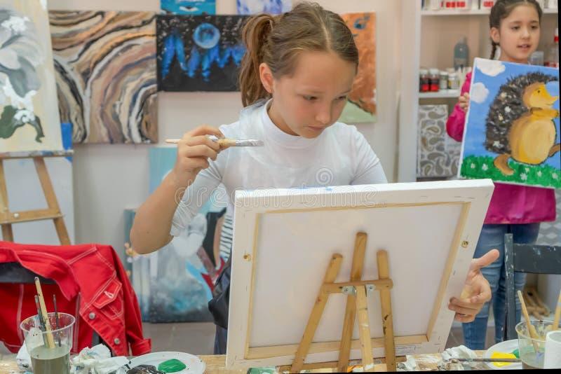 俄罗斯,鞑靼斯坦共和国,2019年4月21日 有刷子的俏丽的女孩在手中 paitning在画架的创造性的青少年的女孩一张图片 ??  库存图片