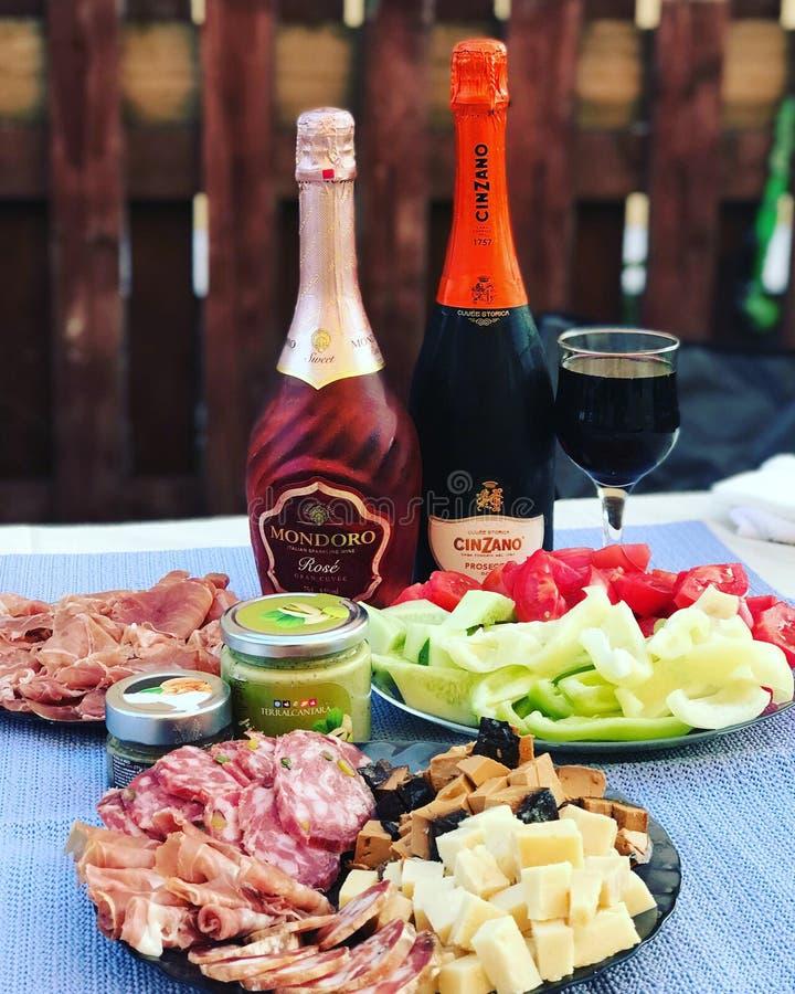 俄罗斯,鞑靼斯坦共和国,2018年7月27日 一个瓶钦扎诺proseco,一个瓶蒙多罗上升了,快餐:jamon,乳酪,pesto,菜 免版税图库摄影
