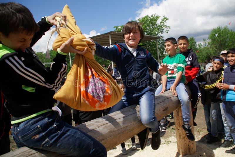 俄罗斯,马格尼托哥尔斯克,- 2019年6月,15日 在假日Sabantuy期间,男孩热心地与在日志的袋子战斗 全国比赛 免版税库存图片