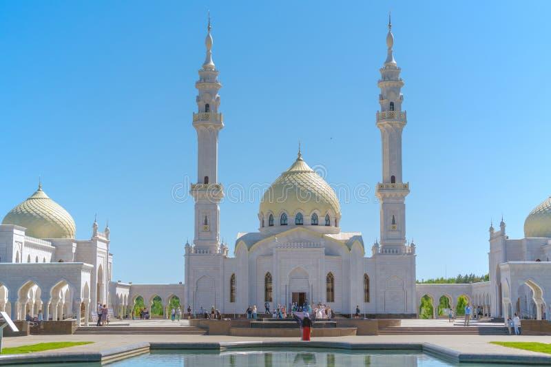 俄罗斯,Bolgar - 2019年6月08日 白色清真寺关闭 人们看清真寺、一名妇女一件红色礼服的和围巾 在附近的湖 免版税图库摄影