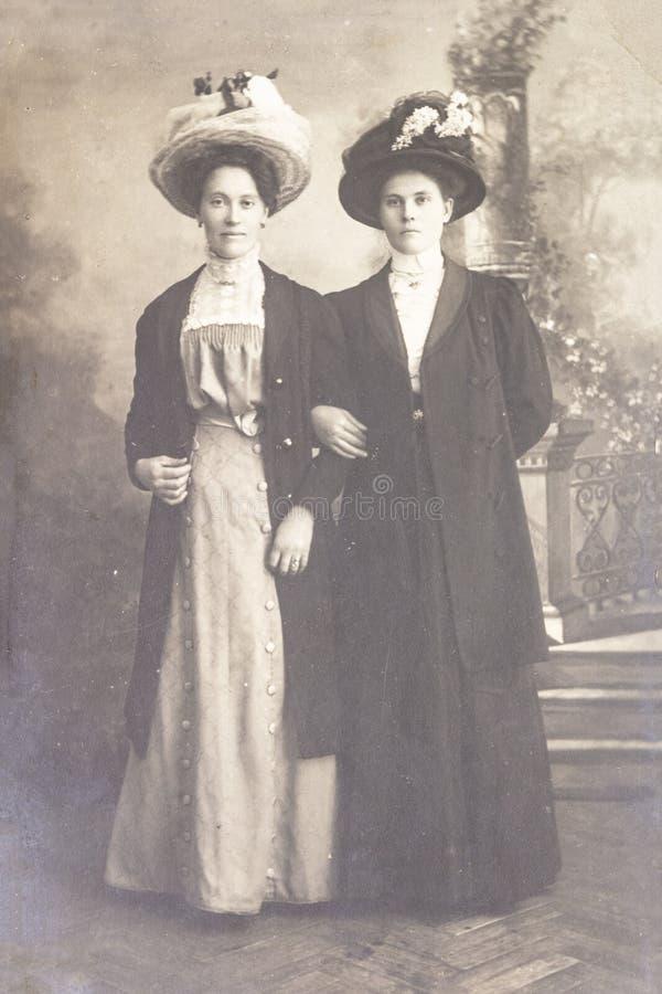 俄罗斯-大约1905-1910:两年轻女人充分的身体射击在演播室,Vintage Carte de Viste Edwardian时代照片 免版税库存图片