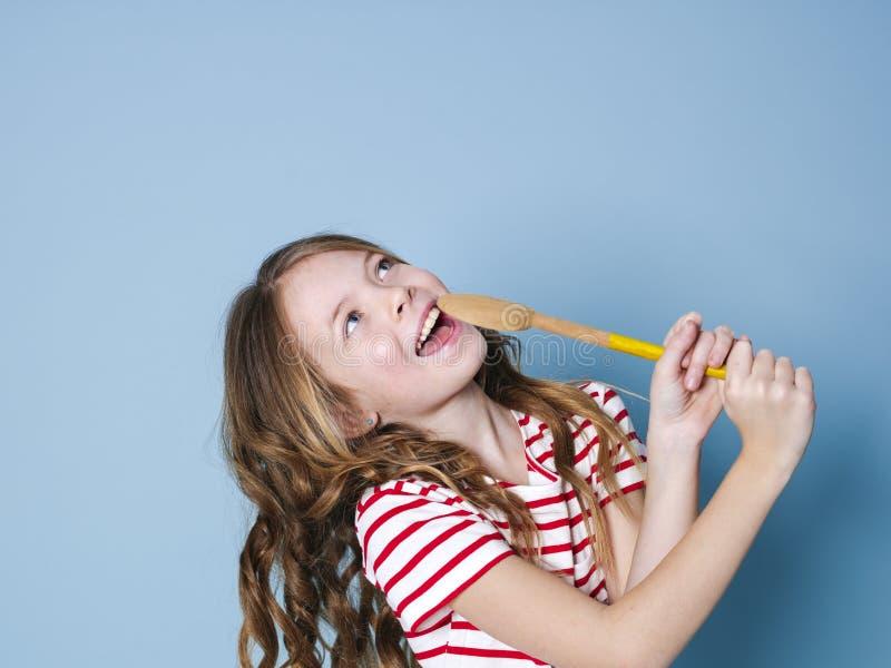 俏丽凉快和少女使用烹调匙子作为话筒并且在蓝色背景前面唱歌和获得很多乐趣 库存图片