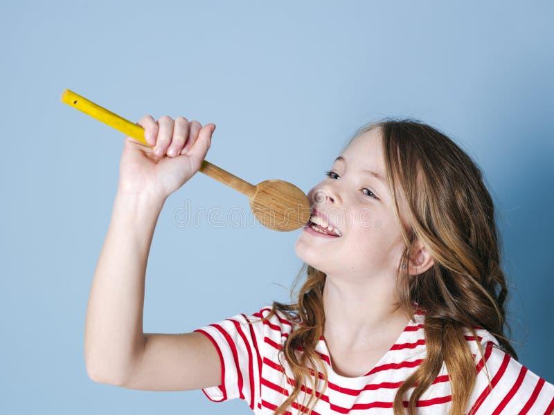 俏丽凉快和少女使用烹调匙子作为话筒并且在蓝色背景前面唱歌和获得很多乐趣 免版税库存图片