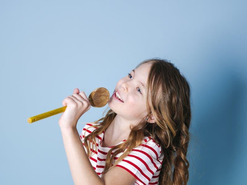 俏丽凉快和少女使用烹调匙子作为话筒并且在蓝色背景前面唱歌和获得很多乐趣 图库摄影