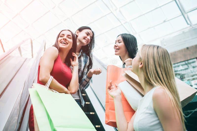 俏丽和愉快的女孩在自动扶梯和笑站立 他们获得乐趣一起 妇女是在大购物 库存照片