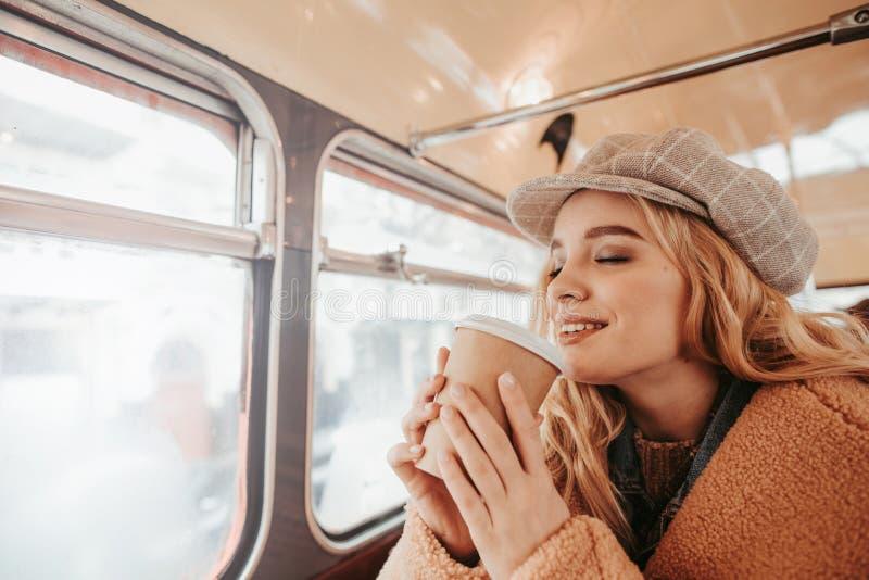 俏丽少女享用在公共汽车咖啡馆的咖啡 免版税库存图片