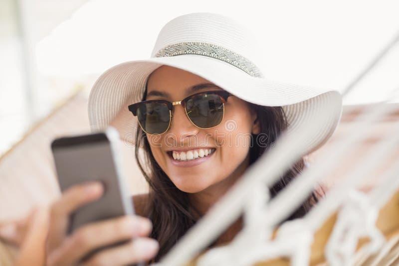 俏丽深色放松在吊床和发短信与她的手机 免版税库存图片