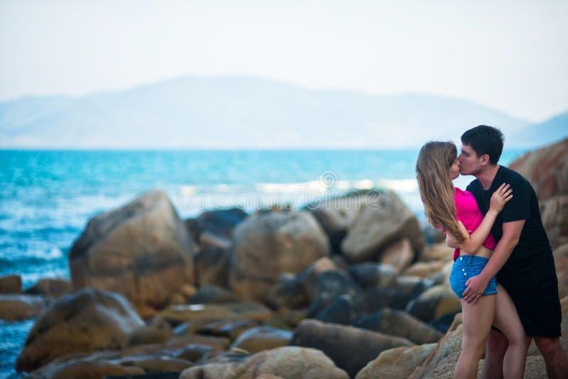 俏丽的亲吻在海的背景的女孩和人 免版税库存图片