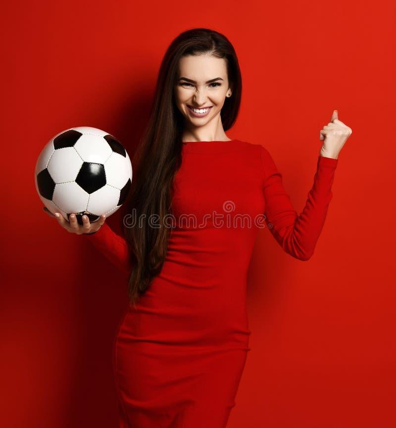 俏丽的体育妇女球员举行足球在手中是庆祝展示胜利成功标志满意对大方的本体拷贝空间 免版税库存图片